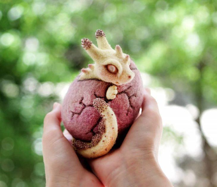 Dragón amarillo recién nacido, saliendo del huevo rosado