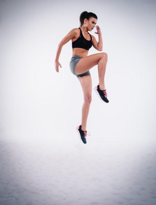 Chica realizando elevaciones de rodilla con ropa deportiva