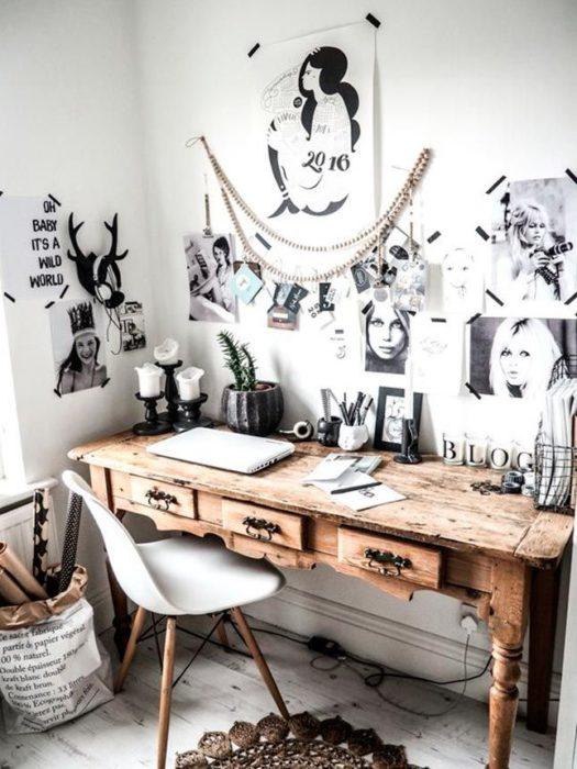 Habitación blanca, silla blanca de cuatro patas y escritorio vintage de madera, con posters pegados en la pared