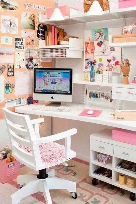 Escritorio alegre, silla, escritorio y repisas blancas, posters y postales pegadas en la pared