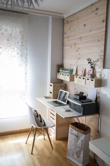 Área del escritorio con fondo de madera, y cajones, además de un bote de basura estilo bolsa de papel