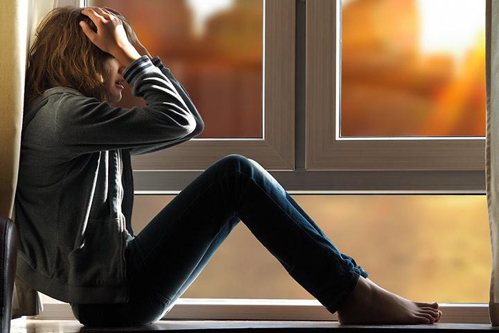 Chica estresada sentada al lado de una ventana