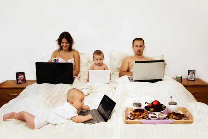 Familia recorstada en la cama usando laptops