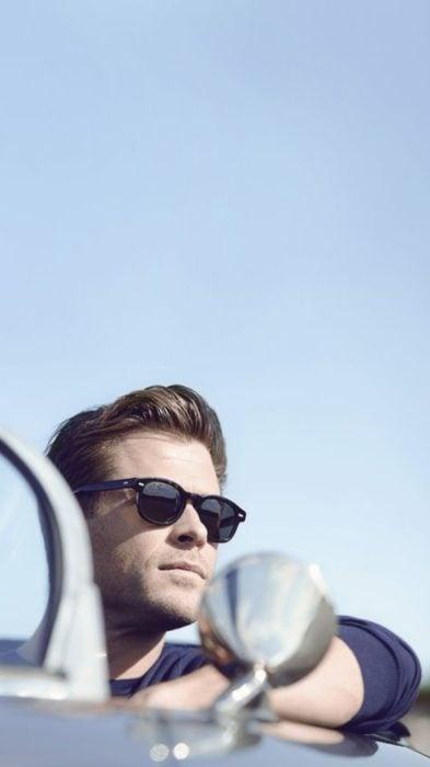 Fondo de pantalla para celular con Chris Hemsworth dentro de un automovil