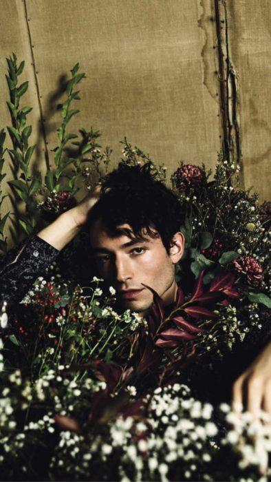 Fondo de pantalla para celular con Ezra Miller recostado entre flores de colores