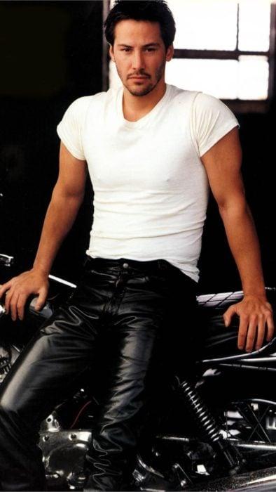 Fondo de pantalla para celular con Keanu Reeves de joven sentado en una motocicleta
