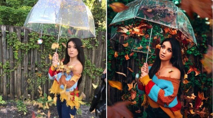 Detrás de cámaras de fotografía de otoño con modelo sosteniendo sombrilla de la que caen hojas secas