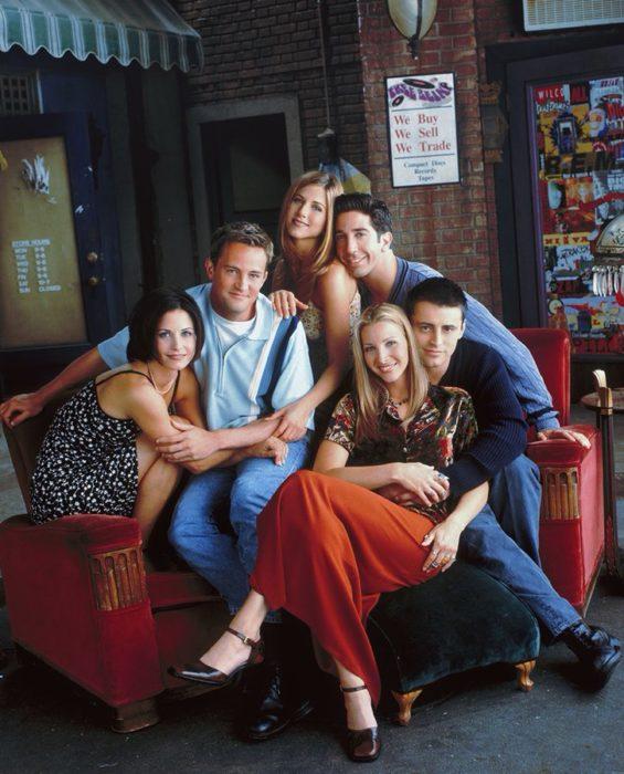 Elenco de Friends reunido en un sofá roja para una foto grupal