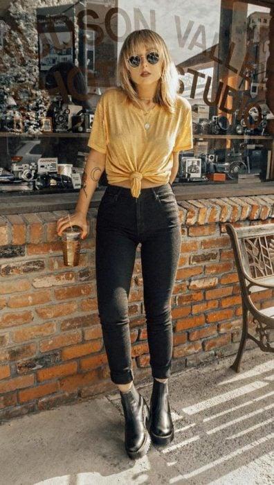 Jeans negros, botines negros y blusa color mostaza anudada