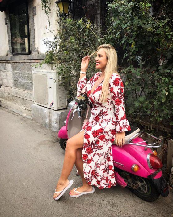 Jen Atkin usando un vestido floreado blanco con rojo, y sandalias recargada en una motoneta