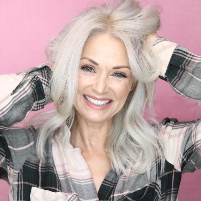 Kathy Jacobs sonriendo y alborotándose el cabello