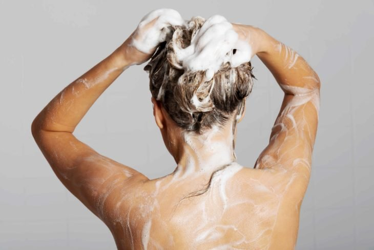 Chica rubia lavando su cabello
