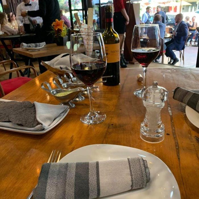 Mesa de madera decorada con platos, servilletas y copas de cristal