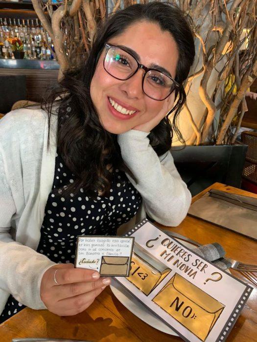 Chica sacando una nota de una invitación a un concierto y sonriendo en un restaurante