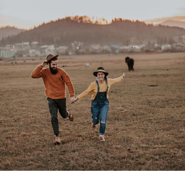 Pareja de novios corriendo por el campo tomados de la mano