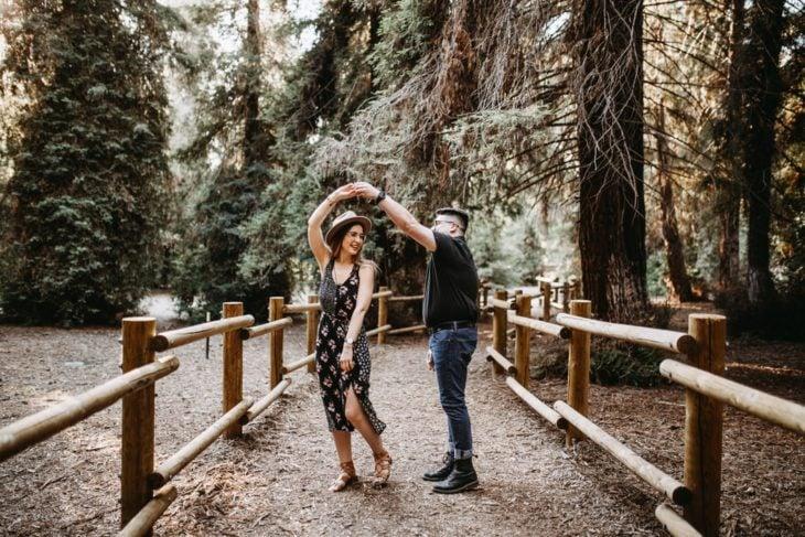 Pareja de novios bailando a mitad del bosques