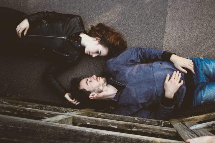 Pareja de novios recostados en el suelo mirándose a los ojos
