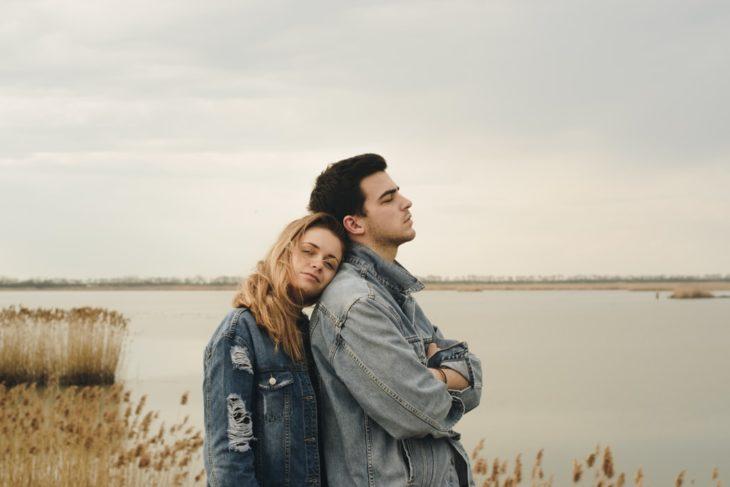 Pareja de novios en el lago, chica recargada en la espalda de su novio