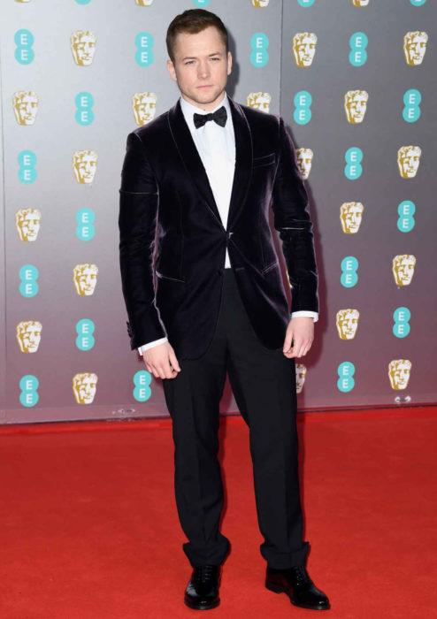 Mejores looks de la alfombra roja de los premios BAFTA 2020; Taron Egerton con traje de terciopelo morado