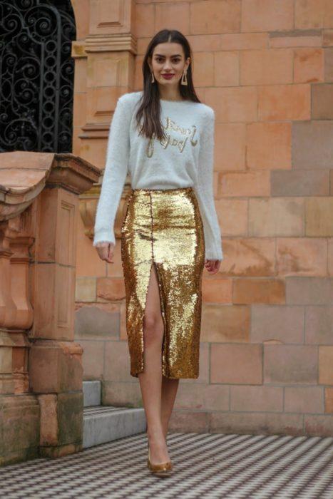 Chica usando una falda de corte lápiz de color dorado con lentejuelas