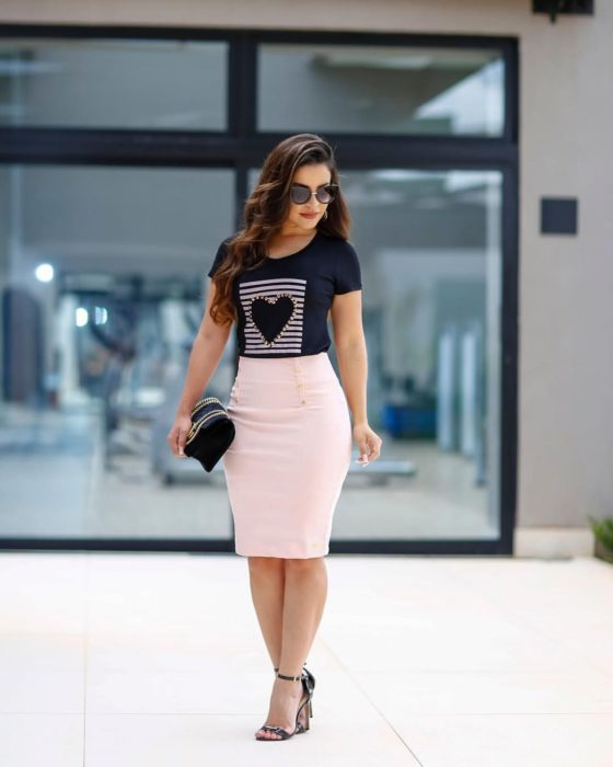 Chica usando una falda de corte lápiz de color rosa
