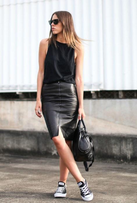 Chica usando una falda de corte lápiz en vinil de color negro