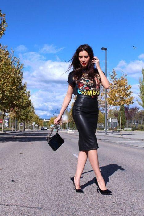 Chica usando una falda de corte lápiz de color negro y de vinil