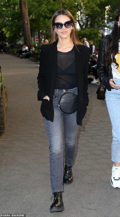 Chica usando jeans con blazer de color negro y botas