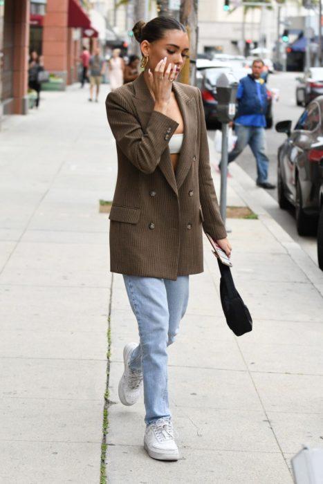 Chica usando un blazer de color café con jeans y tenis