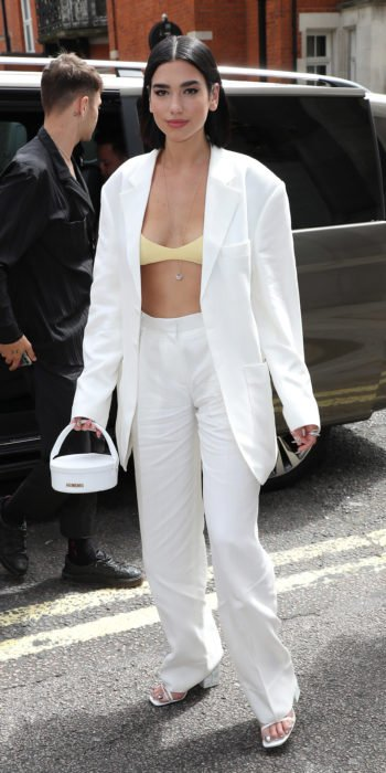 Dua Lipa usando un traje de jean blanco con un top de color amarillo mientras camina por las calles