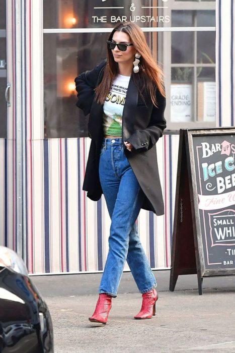 Chica usando un blazer de color negro con jeans y botines de color rojo