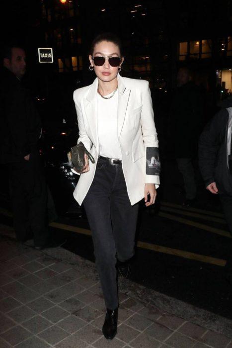 Gigi Hadid caminando por las calles mientras usa un blazer blanco con jeans negros