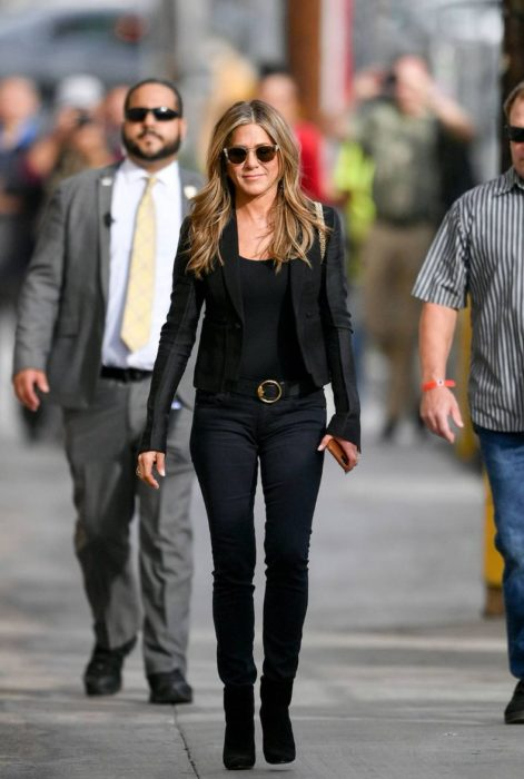 Jennifer Aniston caminando por la calle mientras usa un total black look