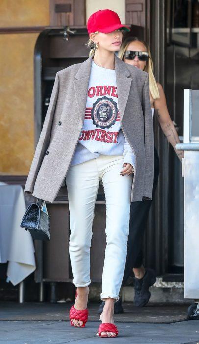 Hailey Baldwin usando jeans y blusa blanca con un blazer de color café