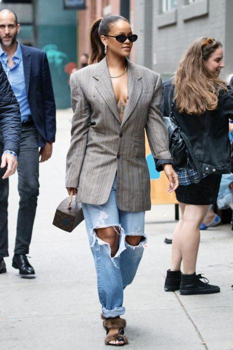 Rihanna caminando por la calle mientras usa un look de blazer con jeans