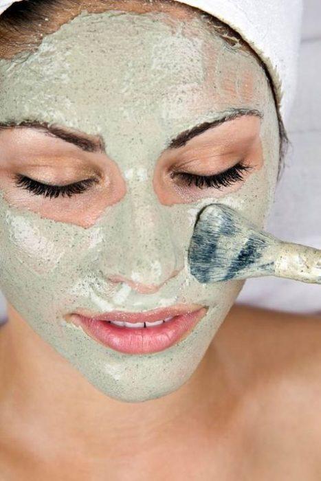 Chica terminando de aplicar una mascarilla sobre su rostro