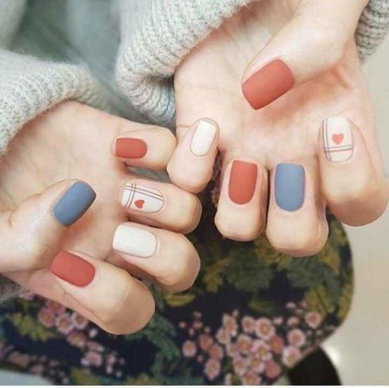 Manicura en uñas cortas en colores azul, blanco y naranja