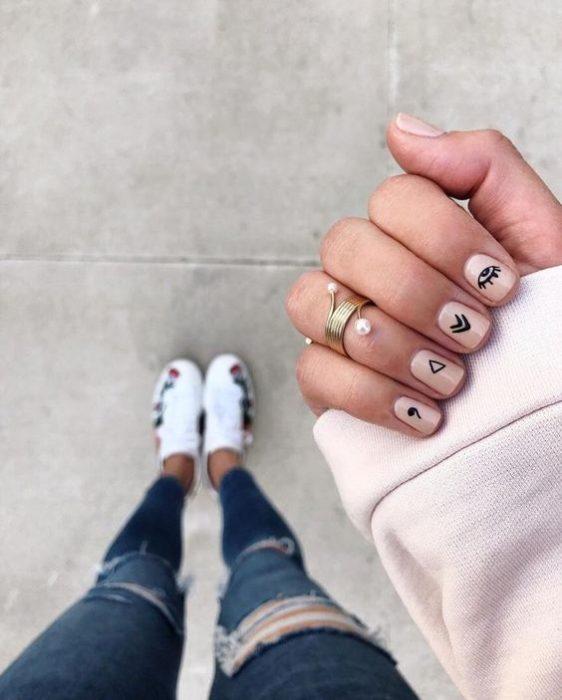 Manicura en uñas cortas de tono rosa palo con stickers negros
