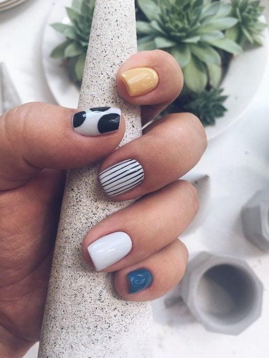 Manicura en tonos azul, blanco, amarillo y con líneas en negro
