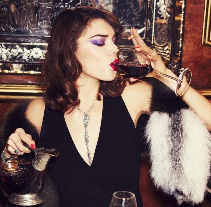 Mujer bebiendo vino y fumando