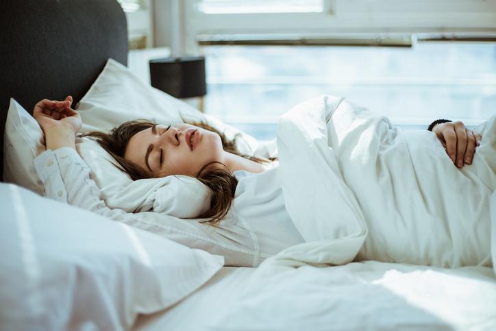 Mujer durmiendo en cama, con pijama y edredón