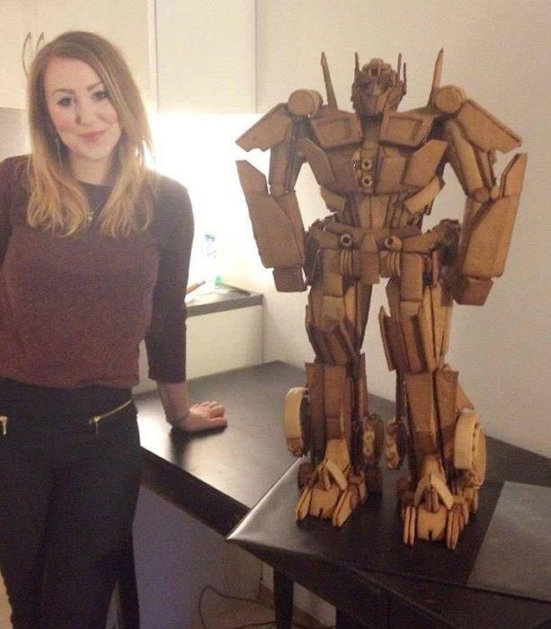 Chica parada junto a una estatua de transformers hecha con pan de gengibre