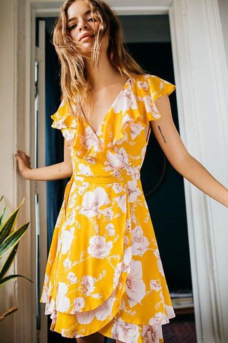 Chica con vestido amarillo y decorado con flores blancas en estilo wrap