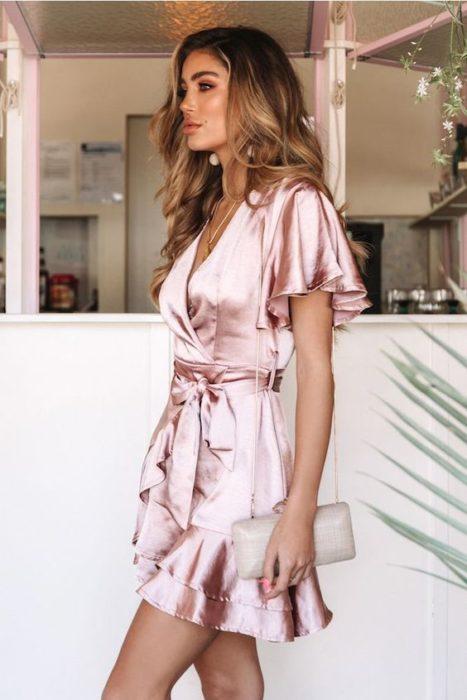 Chica son vestido de tela satín en tono rosa palo