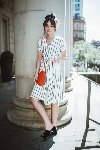 Chica recargada en un pilar con vestido blanco a rayas negras estilo wrap