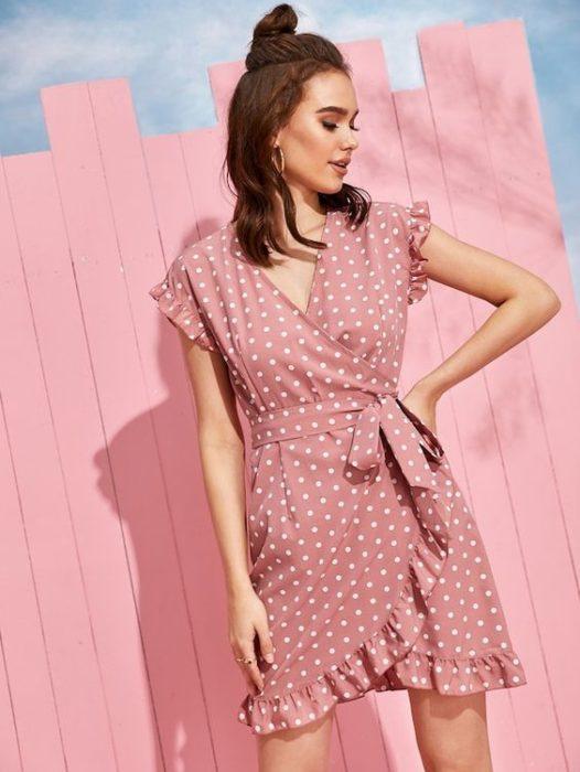 Chica posando con vestido estilo wrap en tono rosa palo con puntos blancos