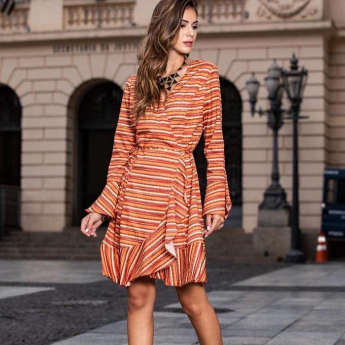 Chica con vestio estilo wrap a rayas en tonos naranjas y amarillos
