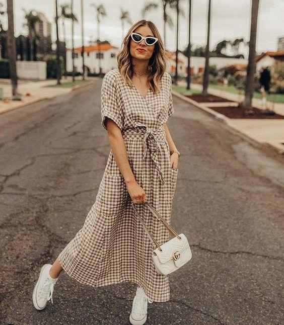 Chica llevando vestido largo con estampado a cuadros estilo wrap