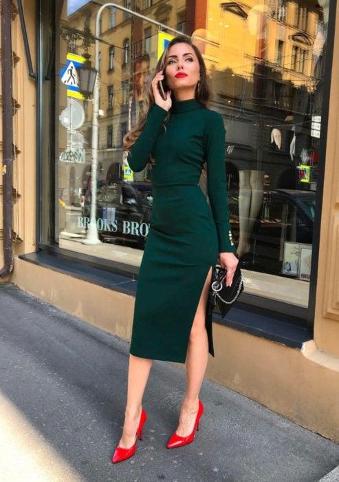 Atuendos formales y juveniles para oficina; mujer hablando por teléfono, vestido ceñido verde de manga larga, con abertura en la pierna, zapatillas rojas
