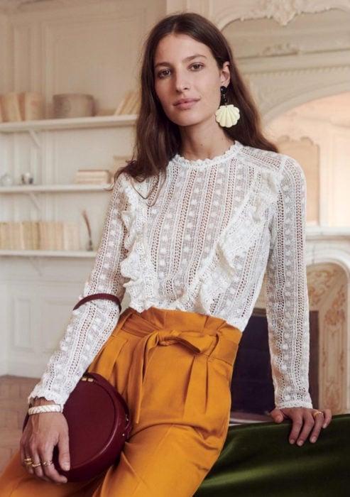 Atuendos formales y juveniles para oficina; blusa blanca de holanes y encaje, aretes de conchas, pantalón anaranjado mostaza